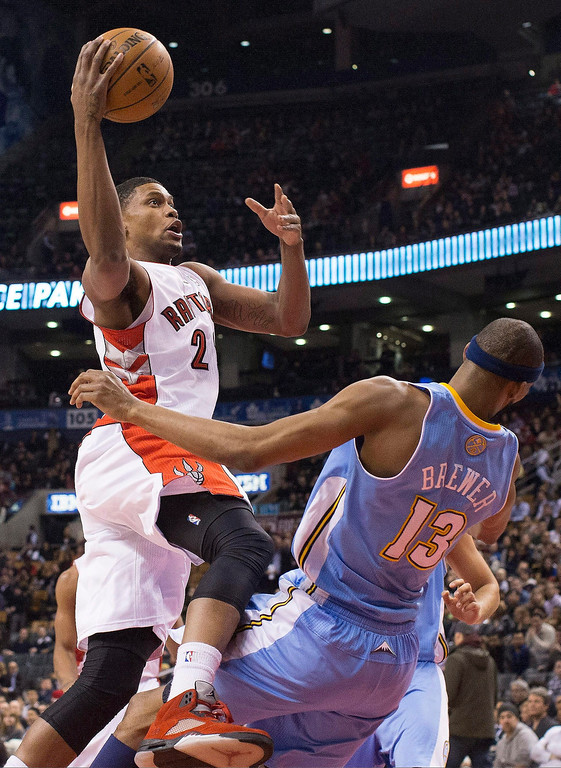 . Toronto Raptors\' Rudy Gay collides with Denver Nuggets\' Corey Brewer as he drives to the basket during the first half of an NBA basketball game in Toronto on Tuesday, Feb. 12, 2013. Gay was called for a foul. (AP Photo/The Canadian Press, Chris Young)