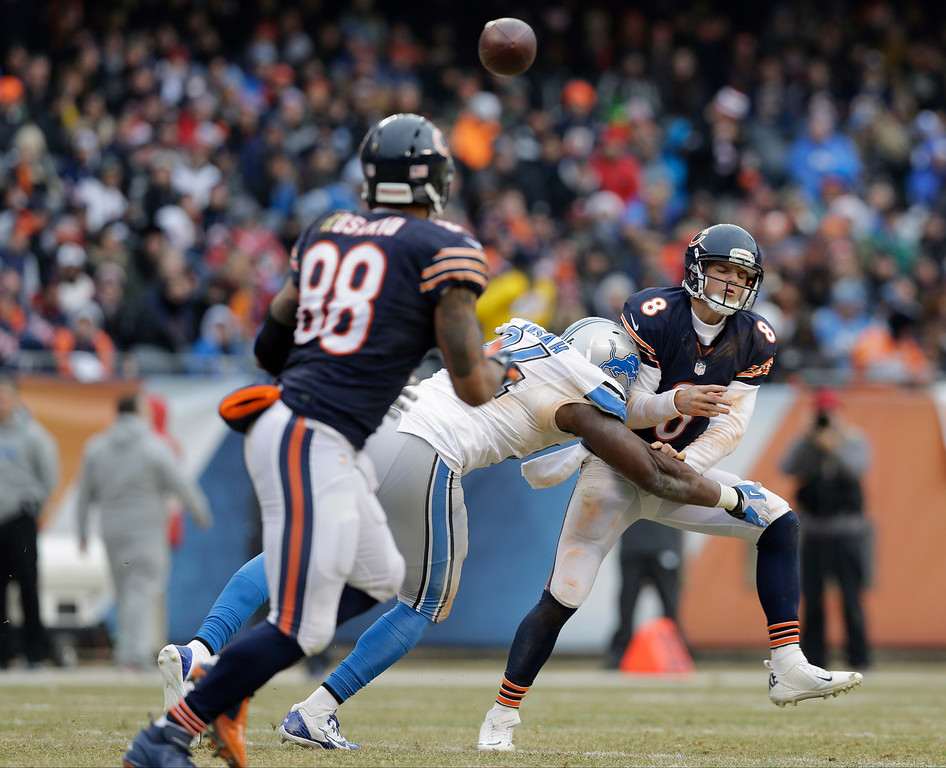 . Chicago Bears quarterback Jimmy Clausen (8) is hit by Detroit Lions defensive end Ezekiel Ansah (94) as Clausen gets off a pass to tight end Dante Rosario (88) in the second half of an NFL football game Sunday, Dec. 21, 2014, in Chicago. (AP Photo/Nam Y. Huh)