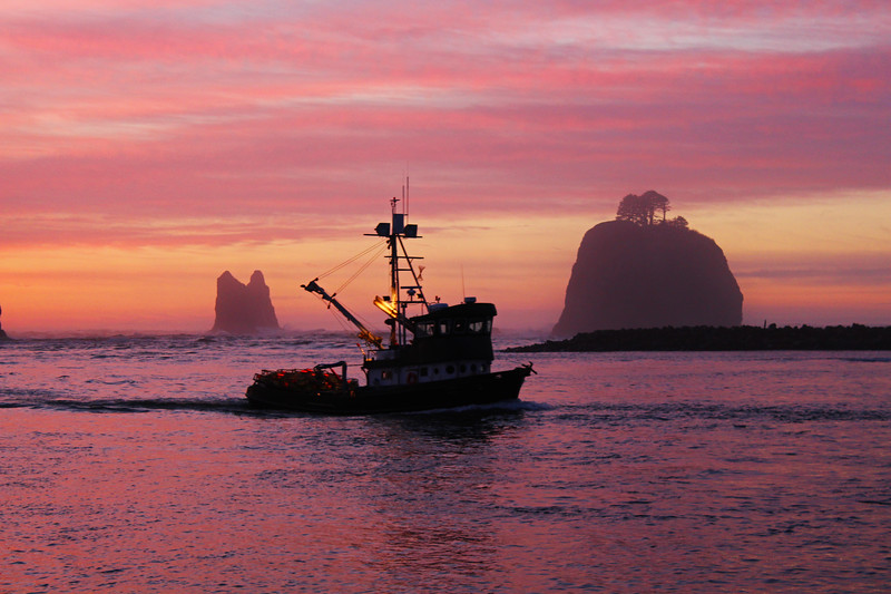 A crabbing vessel returning home to port in Washington during sunset