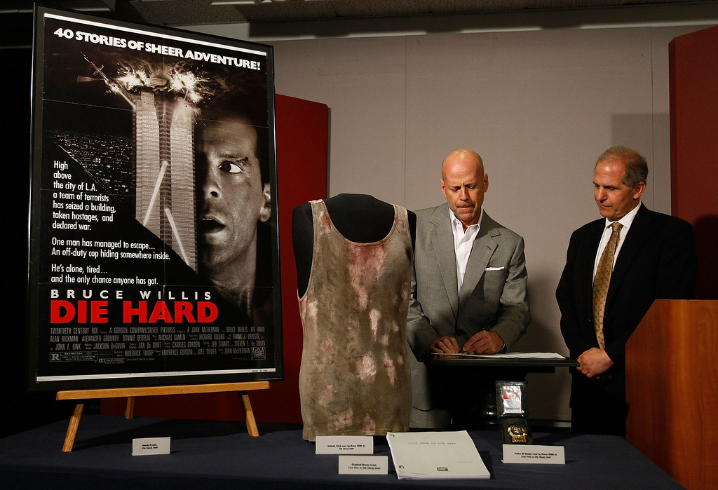""". WASHINGTON - JUNE 27:  Actor Bruce Willis (L) signs an agreement with Director of the National Museum of American History Brent Glass (R) where Willis agreed to donate objects from the \""""Die Hard\"""" series of films to the Smithsonian\'s National Museum of American History June 27, 2007 in Washington, DC. A selection of \""""Die Hard\"""" items will go on display in the new acquisitions case in the museum\'s \""""Treasures of American History\"""" exhibition at the Smithsonian.  (Photo by Win McNamee/Getty Images)"""