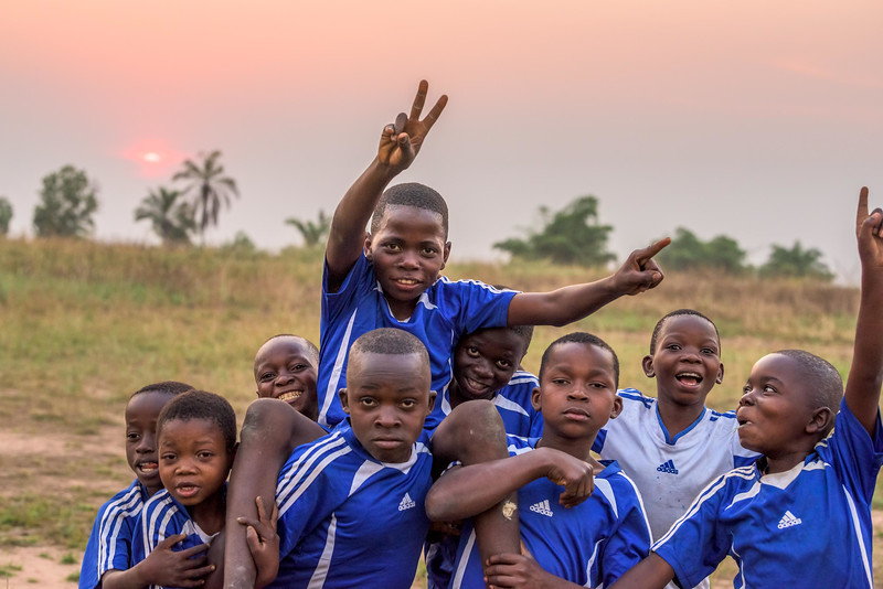 """Wildly enthusiastic celebration when the soccer football team Grace Mukoma, 10 yr-old boy, is on, wins their match at the World Vision Child Friendly Space near his home in Central Kasai Province, Kananga, DRC.  What Grace really loves to do is to go to the Tshilumba Child Friendly Space. It is 2 buildings surrounded by palm trees – out back there's a row of 8 latrines built by WV. There are about 40 kids outside. The morning light is soft on the tall grass. Kids are dancing and doing some fun gymnastics/acrobatics. Grace is small but energetic. He has a nice smile and love to show off how limber he is. He bends and twists, does backflip. Kids form a circle, Grace dances in the middle – most are barefoot in the soft, brown sand. Three boys, Grace, Seba and Kabasela, Grace's best friend, do an acrobatic act that involves the three of them hooked together. Grace loves dancing.   Grace - """"I feel at ease when I'm dancing with my friends and most importantly, it makes me forget about the war.""""  """"When I'm dancing among my friends, I feel very happy and I forget the past.""""  When I'm dancing, I'm not alone. I forget all the things during the war.""""  Background Grace lives with his widowed mom, Mbombo Elize, sister Harriet, 7, and an extended family of relatives, including his widowed grandmother, Kapinga Godelive, 66.  Mbombo has had 4 children, the first when she was 15. 2 died during the time they had to run away because of the war. Now it's just Grace and his sister Harriet, 7.  They live in the Kasai Centrale province in a place called Katoka. It's a rural community. Grace and his family had to run when war broke out in the DRC.  His father was killed. His mother and her 4 children ran about 2 kilometers down the road from his house towards the Lualua River. They hid there for about 3 months. Unfortunately, because of a lack of food and disease, Grace's brother and a sister died. After about 3 months Grace and his family hesitantly made their way back to their house. It """