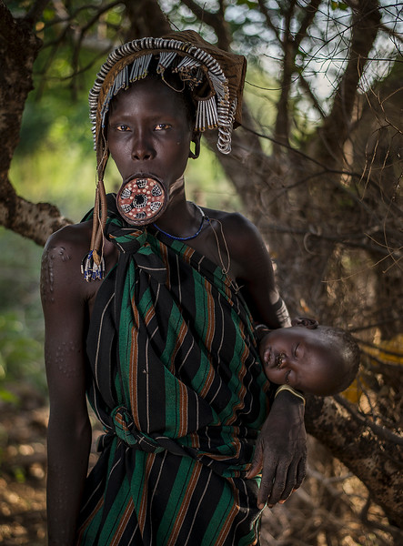 At a young age, to beautify themselves for marriage, most Surma women have their bottom teeth removed and their bottom lips pierced, then stretched, so as to allow insertion of a clay lip plate. Some women have stretched their lips so as to allow plates up to sixteen inches in diameter. Increasing with exposure to other cultures, however, a growing number of girls now refrain from this practice. Their children are sometimes painted with white clay paint, which may be dotted on the face or body.  Southern Ethiopia, 2017