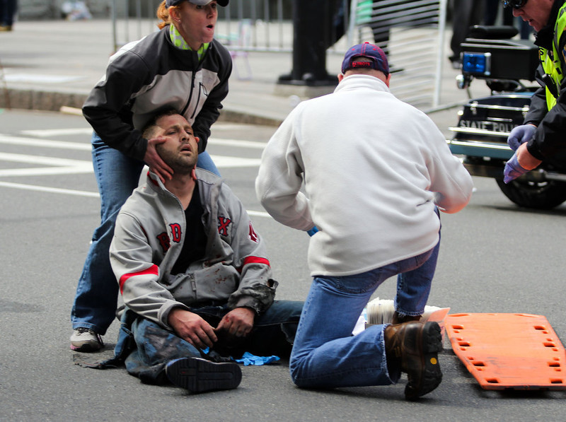 . In this photo provided by The Daily Free Press and Kenshin Okubo, people assist an injured after an explosion at the 2013 Boston Marathon in Boston, Monday, April 15, 2013. Two explosions shattered the euphoria of the Boston Marathon finish line on Monday, sending authorities out on the course to carry off the injured while the stragglers were rerouted away from the smoking site of the blasts. (AP Photo/The Daily Free Press, Kenshin Okubo)