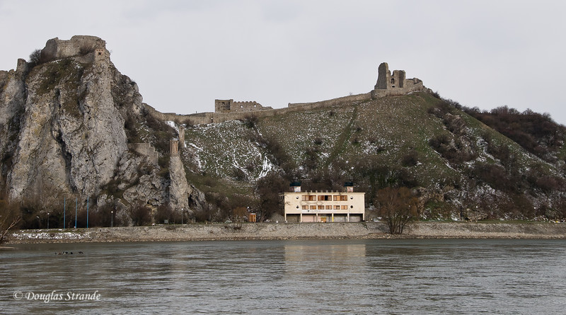 Old castle and a communist building along the Danube