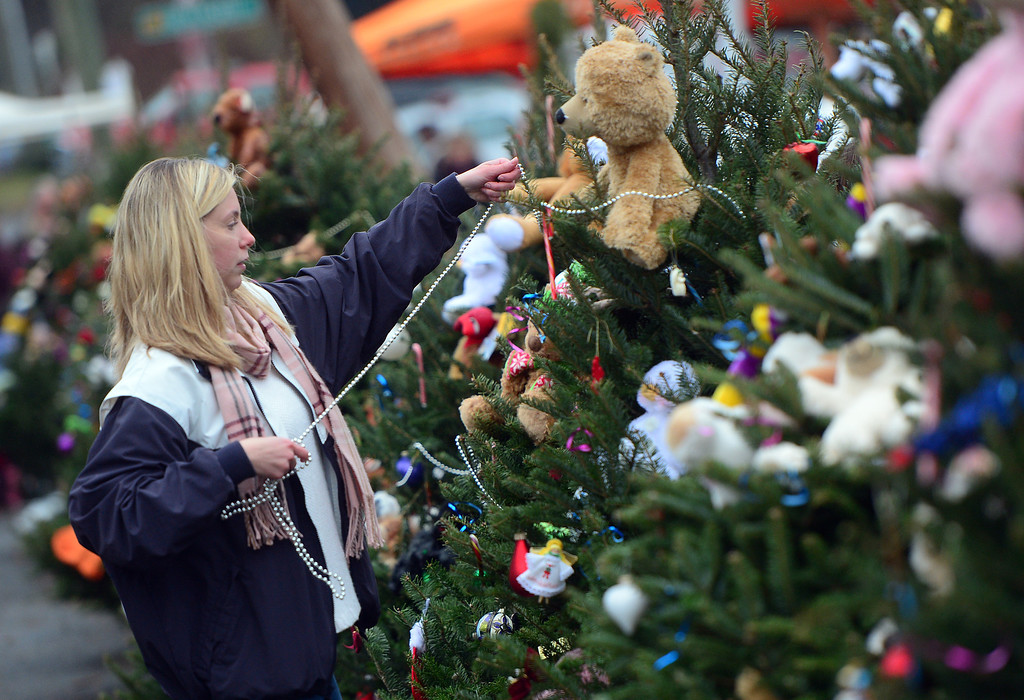 . A teenager decorates Christmas trees set up at a makeshift shrine to the victims of a elementary school shooting in Newtown, Connecticut, December 16, 2012.  A young gunman slaughtered 20 small children and six teachers on December 14,2012 after walking into a school in an idyllic Connecticut town wielding at least two sophisticated firearms.  EMMANUEL DUNAND/AFP/Getty Images