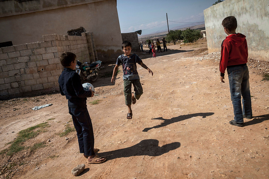 . In this Sunday, Sept. 29, 2013 photo, Syrian children play football outside their homes in Madaya village after school in the public school in the Idlib province countryside of Syria. Millions of Syrian children most of them in government-controlled areas have returned to school in the past two weeks, despite the conflict that according to UNICEF has left 4,000 Syrian schools or one in five damaged, destroyed or sheltering displaced families. (AP Photo)