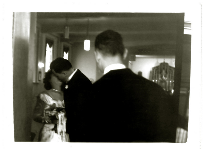 1946. Mom and Dad just after their wedding ceremony, necking in the nave, and Vince crashes the party.