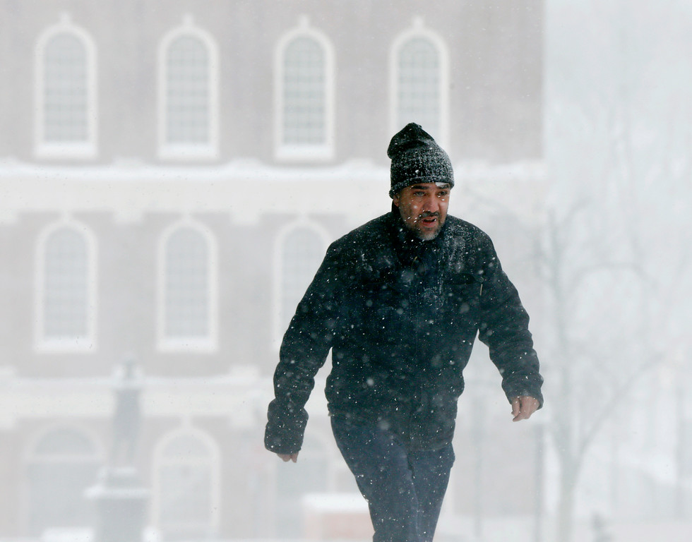 . A pedestrian walks past Faneuil Hall during a snowstorm, Tuesday, March 13, 2018, in Boston. (AP Photo/Michael Dwyer)