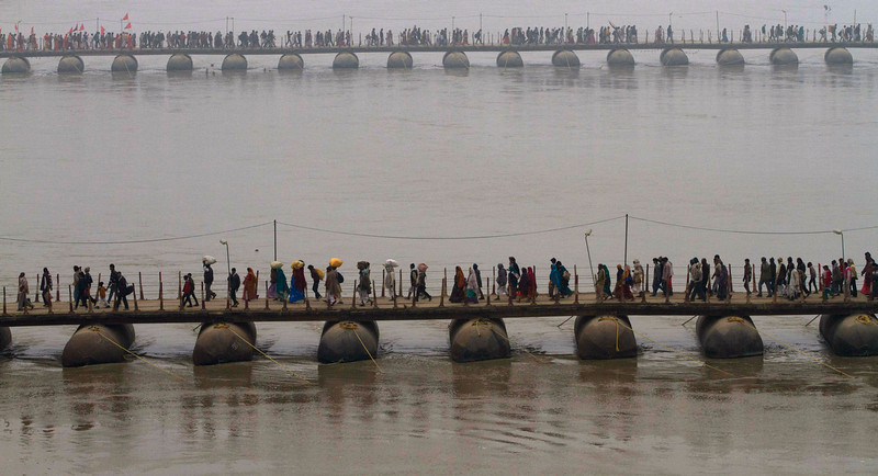 . Indian Hindu devotees walk across a pontoon bridge at the Sangam, the confluence of the Ganges and Yamuna, on \'Mauni Amavasya\' or new moon day, the third and the most auspicious date of bathing during the annual month long Hindu religious fair \'Magh Mela\' in Allahabad, India,  Thursday, Jan. 30, 2014. Hundreds of thousands of Hindu pilgrims take dips in the confluence, hoping to wash away sins during the month long festival. (AP Photo/Rajesh Kumar Singh)