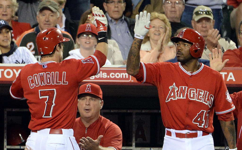 . Los Angeles Angels\' Collin Cowgill (7) high fives teammate Howie Kendrick (47) after scoring on a sac fly ball by Mike Trout (not pictured) in the third inning of a baseball game against the New York Yankees at Anaheim Stadium in Anaheim, Calif., on Tuesday, May 6, 2014.  (Keith Birmingham Pasadena Star-News)