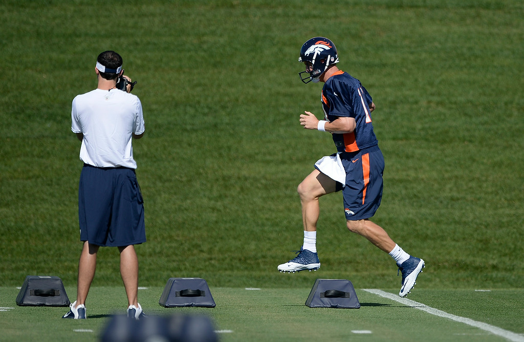 . Denver Broncos quarterback Peyton Manning (18) runs through drills during the start of the Denver Broncos 2014 training camp July 24, 2014 at Dove Valley. (Photo by John Leyba/The Denver Post)