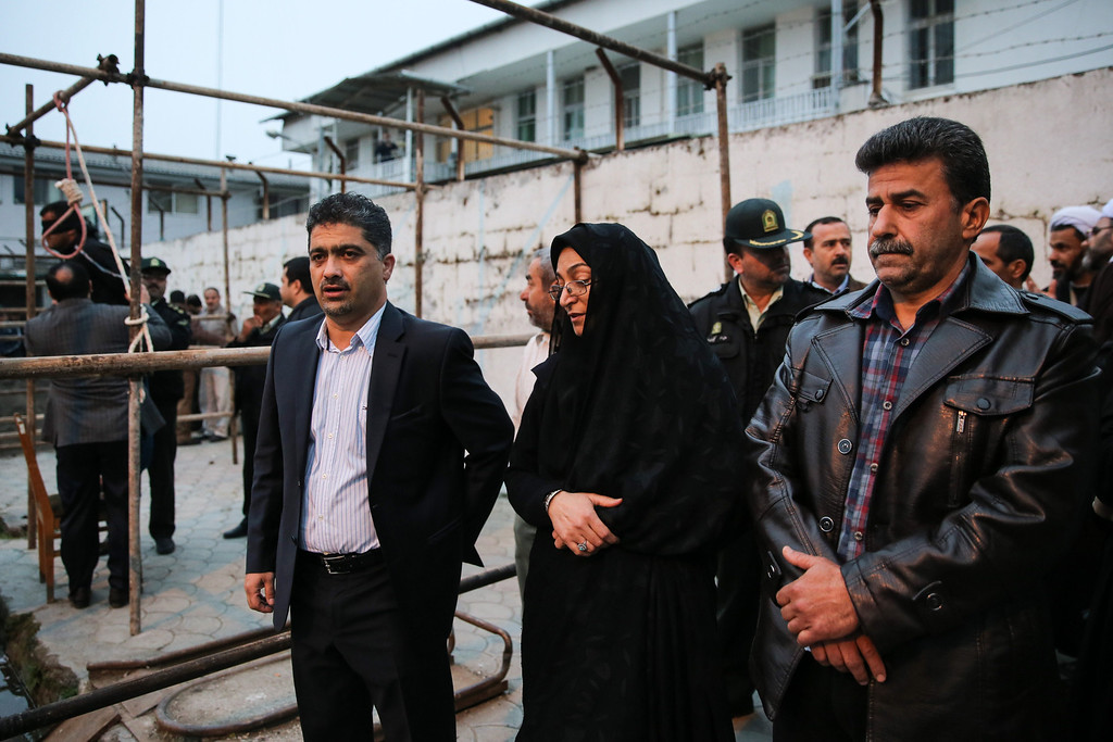. Samereh Alinejad (C), and Abdolghani Hosseinzadeh (R) the parents of Abdolah Hosseinzadeh who was killed by a fellow Iranian, named Balal, in a street fight with a knife in 2007, stand next to the gallows during Balal\'s execution ceremony in the northern city of Nowshahr on April 15, 2014. AFP PHOTO/ARASH KHAMOOSHI/AFP/Getty Images