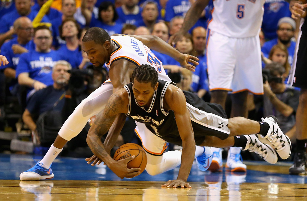 . OKLAHOMA CITY, OK - MAY 27: Kevin Durant #35 of the Oklahoma City Thunder and Kawhi Leonard #2 of the San Antonio Spurs go for a loose ball in the third quarter during Game Four of the Western Conference Finals of the 2014 NBA Playoffs at Chesapeake Energy Arena on May 27, 2014 in Oklahoma City, Oklahoma. (Photo by Ronald Martinez/Getty Images)