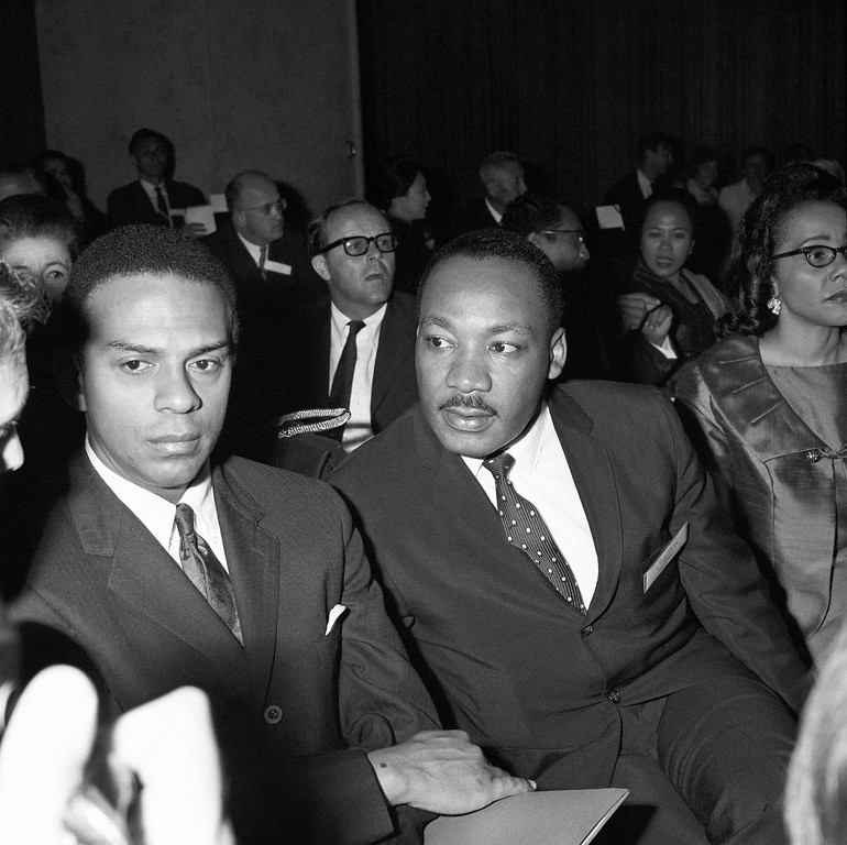 """. The Rev. Martin Luther King turns to answer a question from his seat in Geneva, May 28, 1967, as delegate to \""""Pacem In Terris II\"""" unofficial conference on problems of peace, convoked by U.S. Center for the Study of Democratic Institutions.  At left is his aide, Andrew Young of Atlanta, Georgia. (AP Photo)"""
