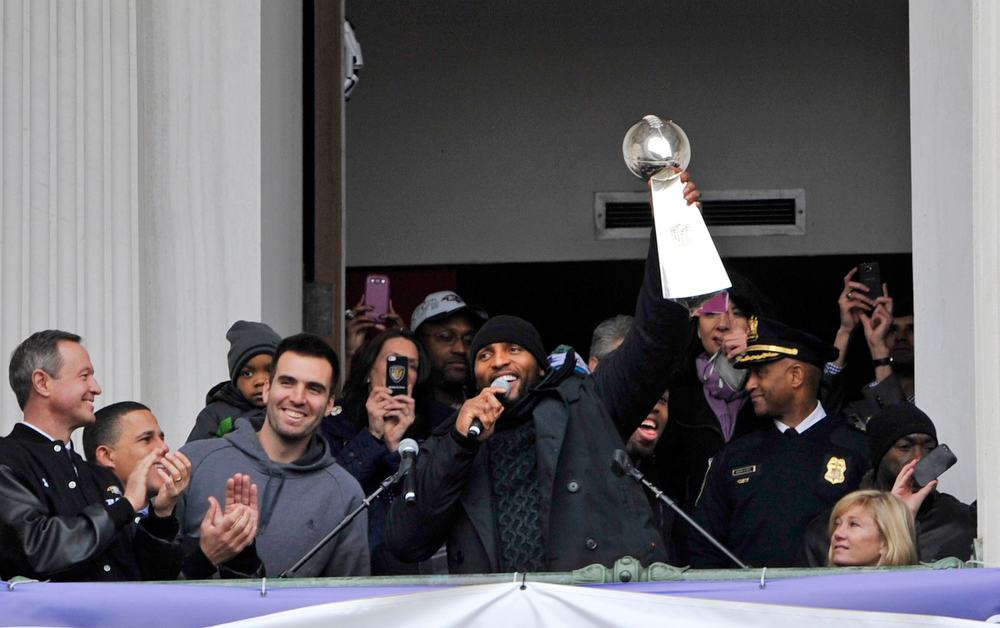 Description of . Baltimore Ravens linebacker Ray Lewis, holding the Vince Lombardi trophy, speaks to fans at a celebration at City Hall at the start of a Super Bowl victory parade Tuesday, Feb. 5, 2013, in Baltimore. Super Bowl MVP and Ravens quarteback Joe Flacco, third from left, smiles. The Ravens defeated the San Francisco 49ers in NFL football's Super Bowl XLVII 34-31 on Sunday. (AP Photo/Gail Burton)