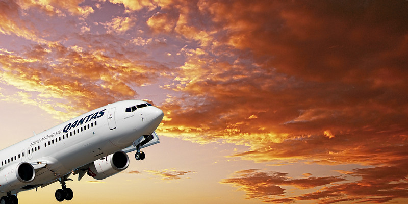 Airborne airliner in flight with yellow altocumulus cloud in sunset sky. Australia.