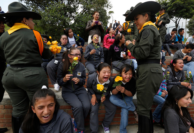 . Police officers hand out long-stemmed yellow roses to school girls during festivities commemorating International Women\'s Day at a public school in Bogota, Colombia, Friday, March 7, 2014. The United Nations global event that celebrates women is observed annually on March 8. (AP Photo/Fernando Vergara)