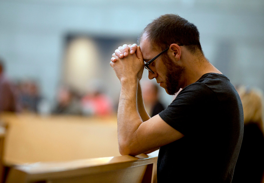 . An unidentified mourner clasps his hands in prayer while attending a memorial Mass for the six people killed Tuesday in a Berkeley apartment building balcony collapse, on Wednesday, June 17, 2015, at the Cathedral of Christ the Light in Oakland, Calif. (D. Ross Cameron/Bay Area News Group)