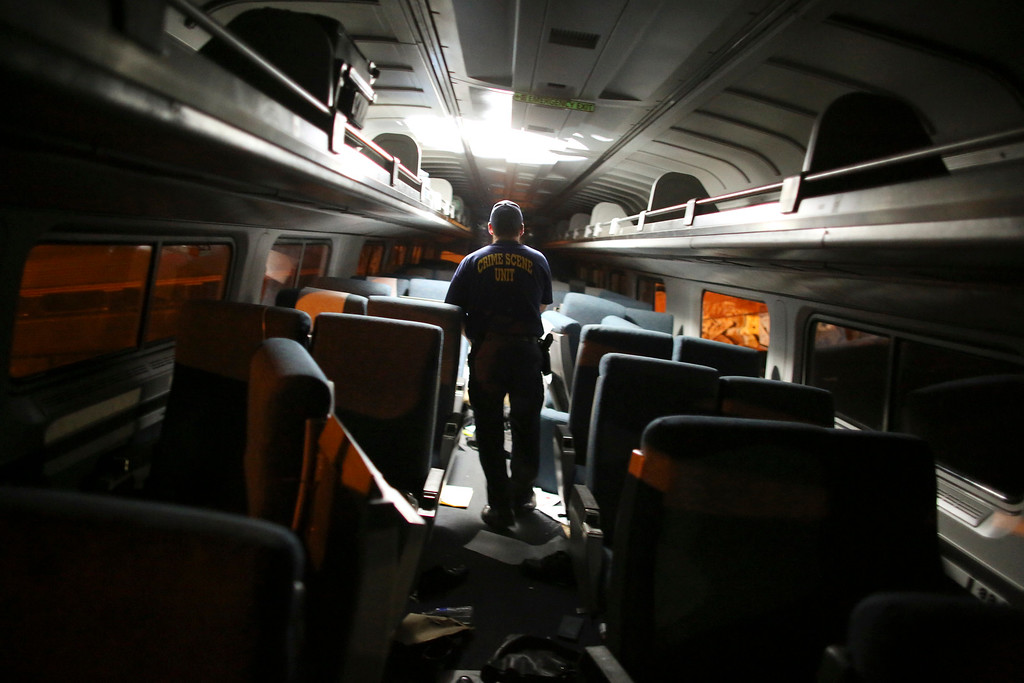 . A crime scene investigator looks inside a train car after a train wreck, Tuesday, May 12, 2015, in Philadelphia. An Amtrak train headed to New York City derailed and crashed in Philadelphia. (AP Photo/Joseph Kaczmarek)