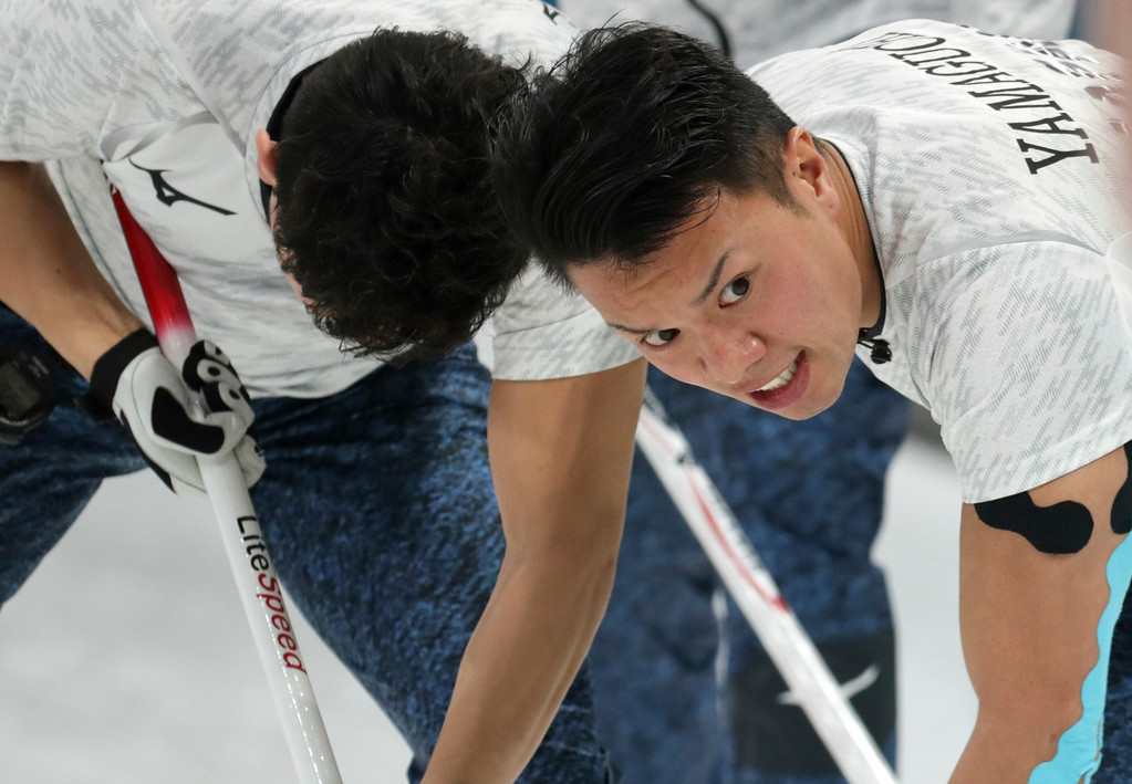 . Japan\'s Tsuyoshi Yamaguchi, right, sweeps ice during their men\'s curling match against Sweden at the 2018 Winter Olympics in Gangneung, South Korea, Sunday, Feb. 18, 2018. (AP Photo/Aaron Favila)