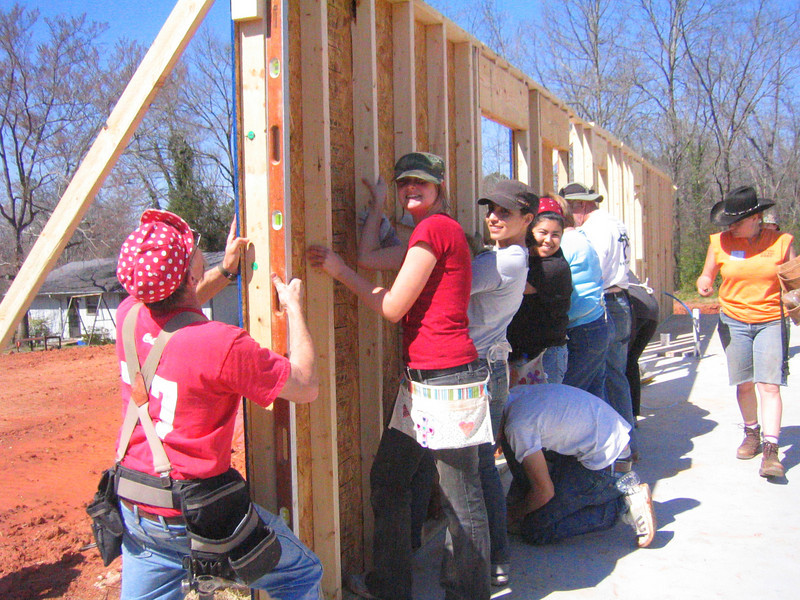 08 03-10 FSU and other volunteers hold outside wall while it is being secured in place.