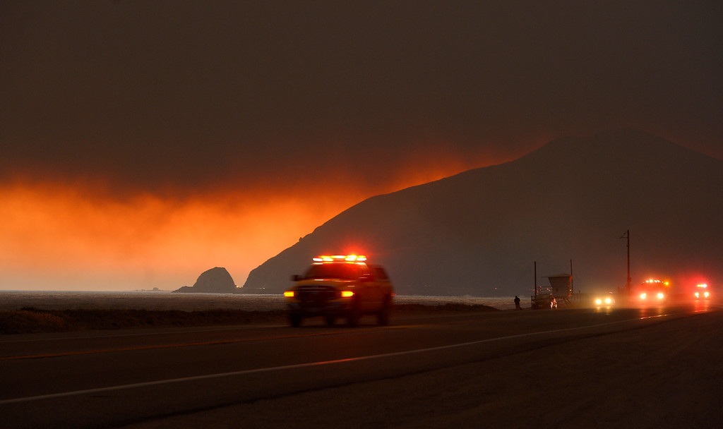 . Fire department personnel drive along Pacific Coast Highway near Point Mugu as a thick layer of smoke sits overhead during a wildfire that burned several thousand acres, Thursday, May 2, 2013, in Ventura County, Calif.   (AP Photo/Mark J. Terrill)