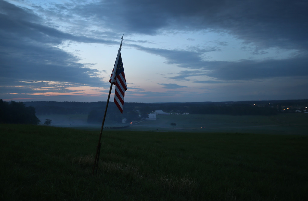 . GETTYSBURG, PA - JUNE 28:  An American flag flies over the field of battle at dusk after the first day of the Blue Gray Alliance re-enactment of the 150th anniversary of the Battle of Gettysburg on June 28, 2013 in Gettysburg, Pennsylvania. Some 8,000 re-enactors are participating in the event, marking the July 1-3, 1863 Battle of Gettysburg, considered the turning point in favor of the Union in the Civil War. Union and Confederate armies suffered a combined total of some 46,000-51,000 casualties in the battle, the highest of any conflict of the war.  (Photo by John Moore/Getty Images)