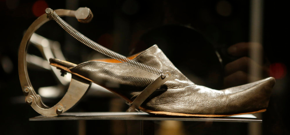 Description of . Kei Kagami's oxidized metal and leather footwear on display at the