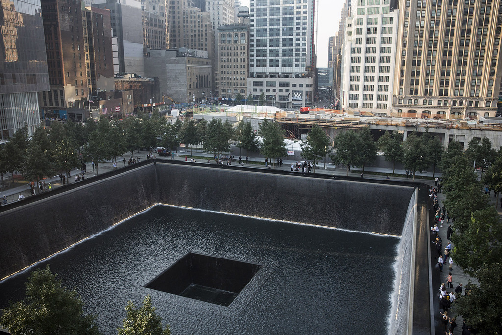 . People gather around the South Tower pool during memorial ceremonies for the twelfth anniversary of the terrorist attacks on lower Manhattan at the World Trade Center site on September 11, 2013 in New York City.  (Photo by Andrew Burton/Getty Images)