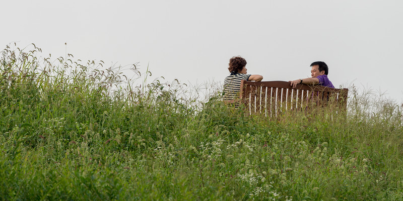 Couple sitting on bench in park, Seoul, South Korea