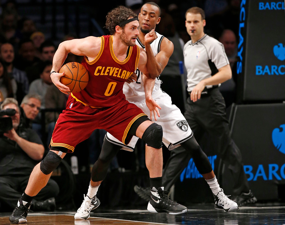 . Brooklyn Nets guard Markel Brown (22) defends Cleveland Cavaliers forward Kevin Love (0) in the second half of an NBA basketball game, Wednesday, Jan. 20, 2016, in New York. Love and LeBron James led the Cavaliers with 17 points each in the Cavs 91-78 victory over the Nets. (AP Photo/Kathy Willens)