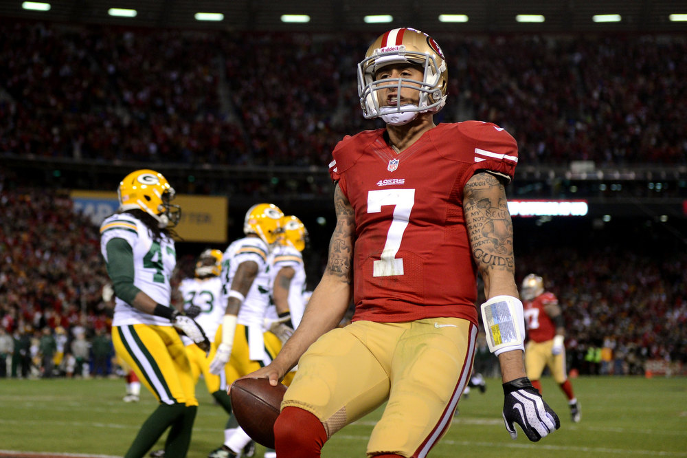 Description of . Quarterback Colin Kaepernick #7 of the San Francisco 49ers celebrates after running in a touchdown in the first quarter against the Green Bay Packers during the NFC Divisional Playoff Game at Candlestick Park on January 12, 2013 in San Francisco, California.  (Photo by Harry How/Getty Images)