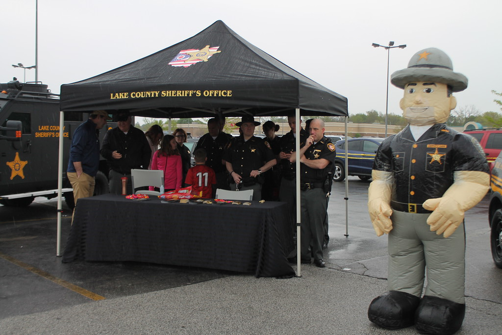 . Kristi Garabrandt � The News-Herald <br> Members of the Lake County Sheriff Department gather under the tent as rain hits during the 36th Annual Heroes Day held at Great Lakes Mall, May 12, 2018.