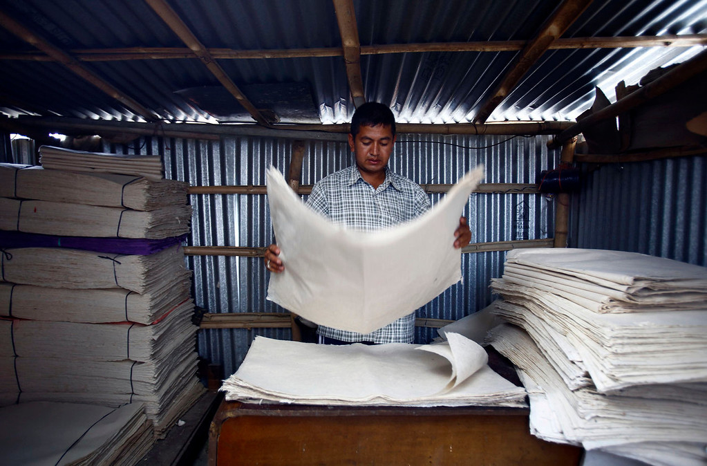 . Factory owner Shyam Hari Kadel arranges newly made Handmade Nepali Lokta Paper at his factory in Bhaktapur July 17, 2013. Lokta papers are made up of fibrous inner bark of Lokta bushes that are found above 5,000 m above sea level. According to factory owner Shyam Hari Kadel most of the papers that he produced are exported to countries like Germany and Britain.  REUTERS/Navesh Chitrakar