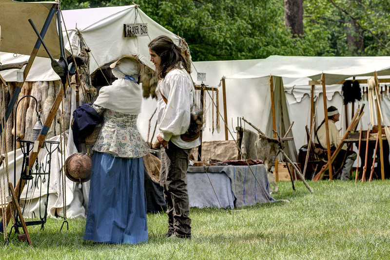 Reenactors browse the goods for sale along Sutler Row during the Siege of Fort Watauga at Sycamore Shoals State Park in Elizabethton, VA on Saturday, May 17, 2014. Copyright 2014 Jason Barnette  The Siege of Fort Watauga is a two-day reenactment held each year at the recreation of the fort inside Sycamore Shoals State Historic Park. The reenactment brings in dozens of reenactors and hundreds of visitors as they tell the story of an attack on the early settlers village by Dragging Canoe, and how they successfully defended themselves. During the reenactment, the fort is open to the public with demonstrations of all areas of early settler life on the frontiers.