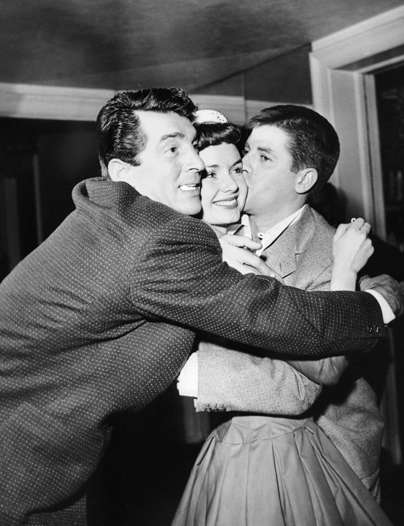 """. Dean Martin, Debbie Reynolds and Jerry Lewis embrace each other upon acknowledging the news on Dec. 28, 1954, that they were voted the \""""Most Cooperative Stars of 1954\"""" by the Hollywood, Women\'s Press Club. Location unknown. (AP Photo)"""
