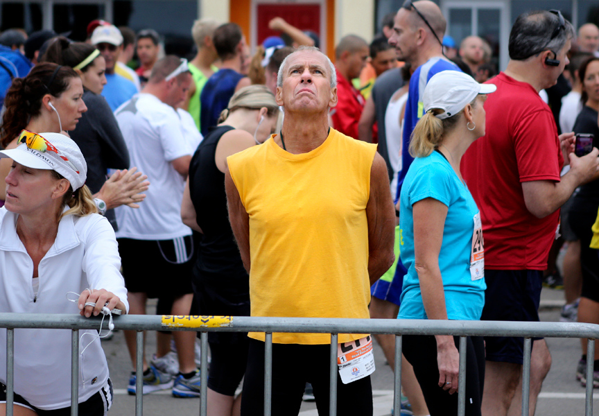 . John Plain from Kingsburg concentrates as he stretches out his muscles at the starting line of the 2013 Wharf to Wharf on Beach Street in Santa Cruz on Sunday. (Kevin Johnson/Sentinel)