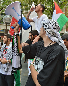 Man on top of anothers shoulders, speaks using bullhorn being held by other protester wearing keffiyeh on head, Palestinian flag in background.
