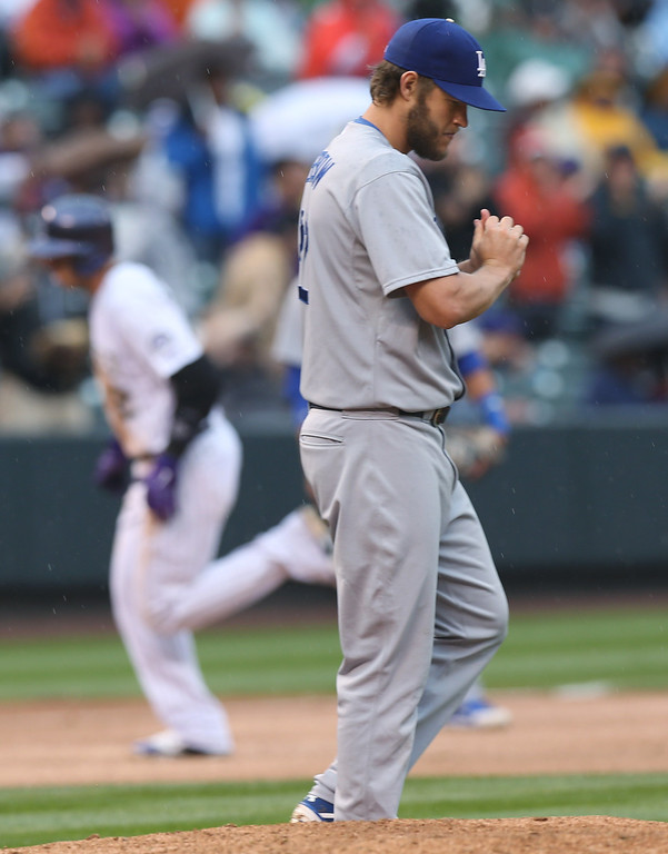 . Los Angeles Dodgers starting pitcher Clayton Kershaw, front, reacts after giving up a solo home run to Colorado Rockies\' Troy Tulowitzki, back, in the fourth inning of a baseball game in Denver on Sunday, June 8, 2014. (AP Photo/David Zalubowski)