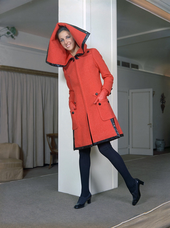 . The large hood is the characteristic of this red woolen coat, bordered with black leather trimmings, a creation by the Fontana Sisters fashion house of Rome for its fall and winter collection, July 18, 1968. It is worn with black leather and chamois shoes, black woolen stockings and red leather gloves. (AP Photo/Mario Torrisi)