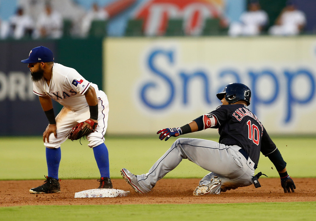 . Cleveland Indians\' Edwin Encarnacion (10) slides safe on his double ahead of the throw to Texas Rangers second baseman Rougned Odor, left, during the fifth inning of a baseball game, Saturday, July 21, 2018, in Arlington, Texas. (AP Photo/Jim Cowsert)