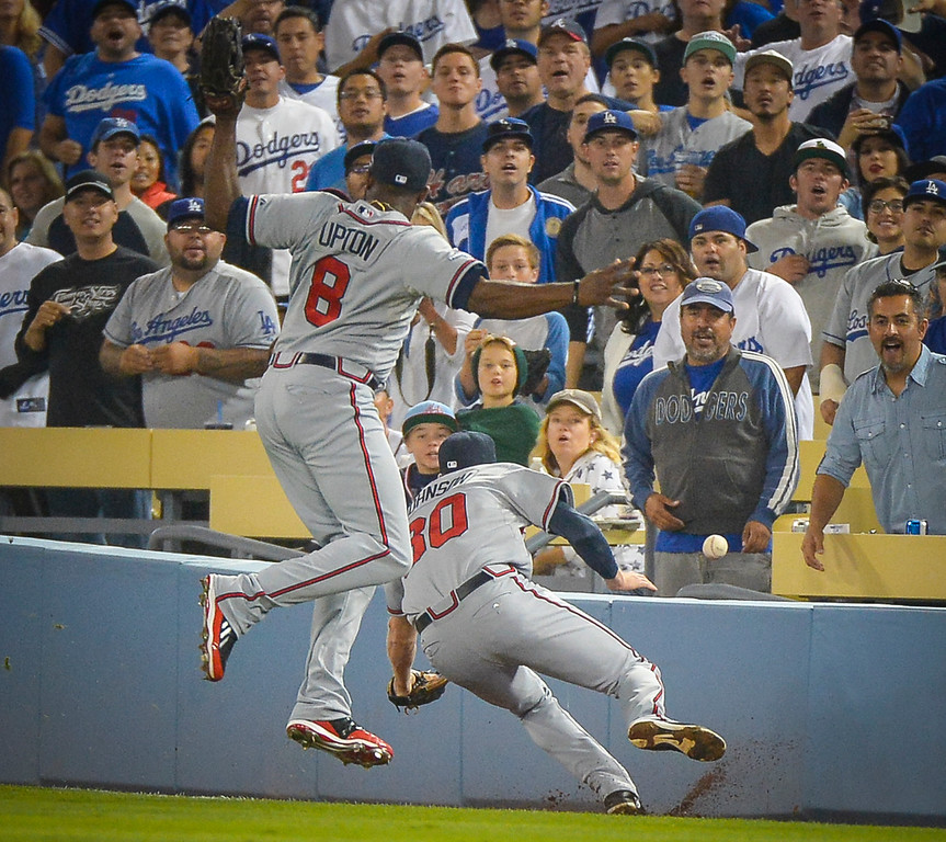 . Atlanta\'s Justin Upton and Elliot Johnson can\'t get this hit by Dodgers\' Mark Ellis during game action Monday, October 7, 2013 ( Photo by Andy Holzman/Los Angeles Daily News )