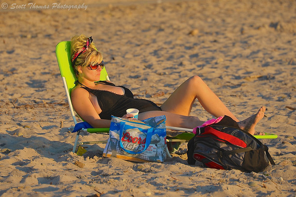A woman lounging on the beach at Brennan's Beach RV Campground and Resort near Pulaski, New York.