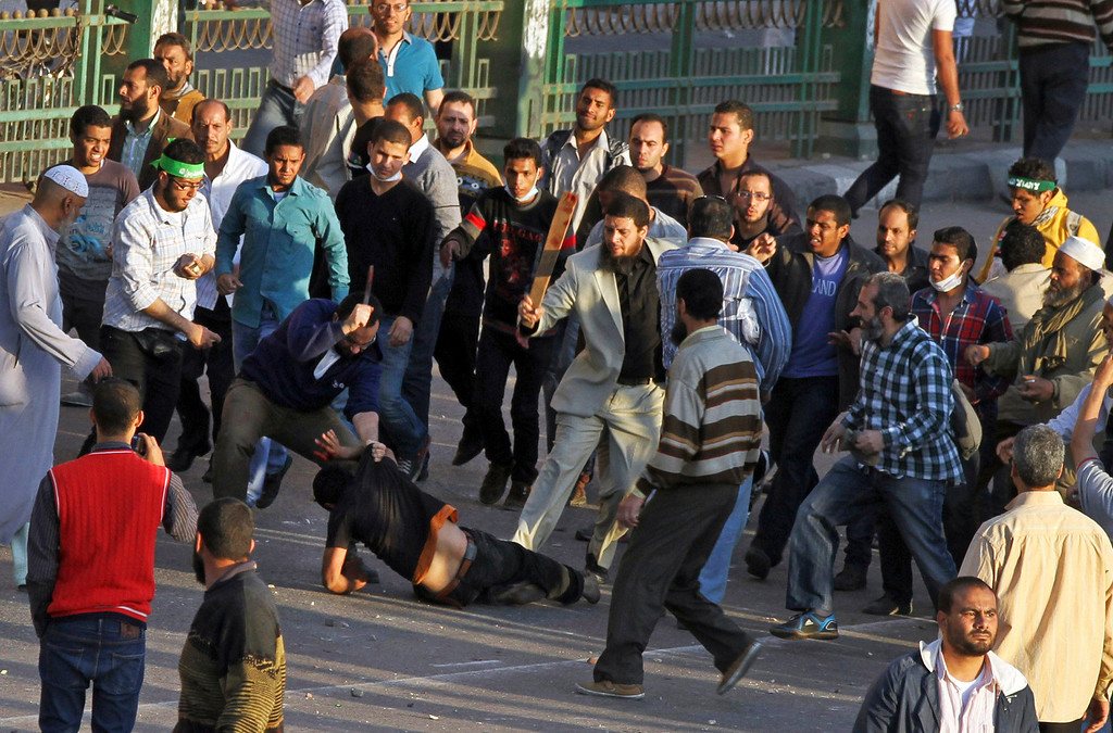 . Muslim Brotherhood supporters beat a protester in Tahrir Square, as supporters and opponents of Egypt\'s Islamist president battle in Cairo, Egypt, Friday, April 19, 2013. (AP Photo/Ahmed Gomaa, File)