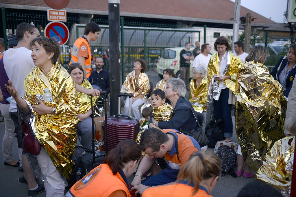 . Victim keep wrapped under thermal blankets at the site of a train accident on July 12, 2013 at the railway station of Bretigny-sur-Orge, near Paris. At least six people were killed and dozens injured today after a speeding train derailed at a station in the southern suburbs of Paris, officials said. AFP PHOTO / MARTIN  BUREAU/AFP/Getty Images