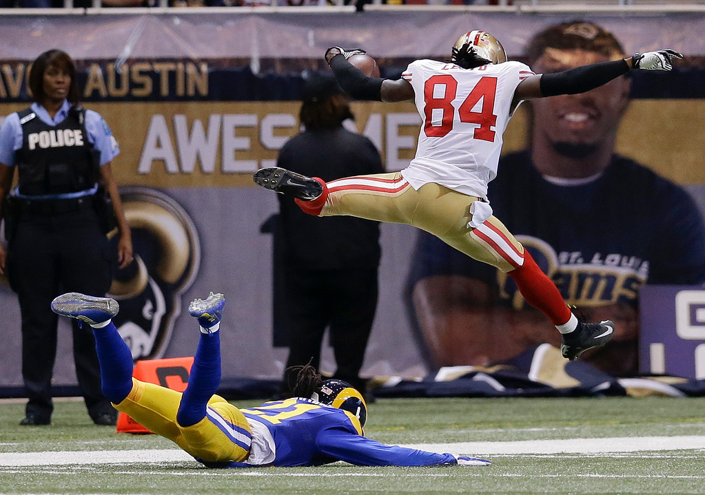 . San Francisco 49ers wide receiver Brandon Lloyd (84) jumps into the end zone ahead of St. Louis Rams cornerback Janoris Jenkins (21) as Lloyd scores a touchdown on an 80-yard pass play in the second quarter of an NFL football game Monday, Oct. 13, 2014, in St Louis. (AP Photo/Scott Kane)