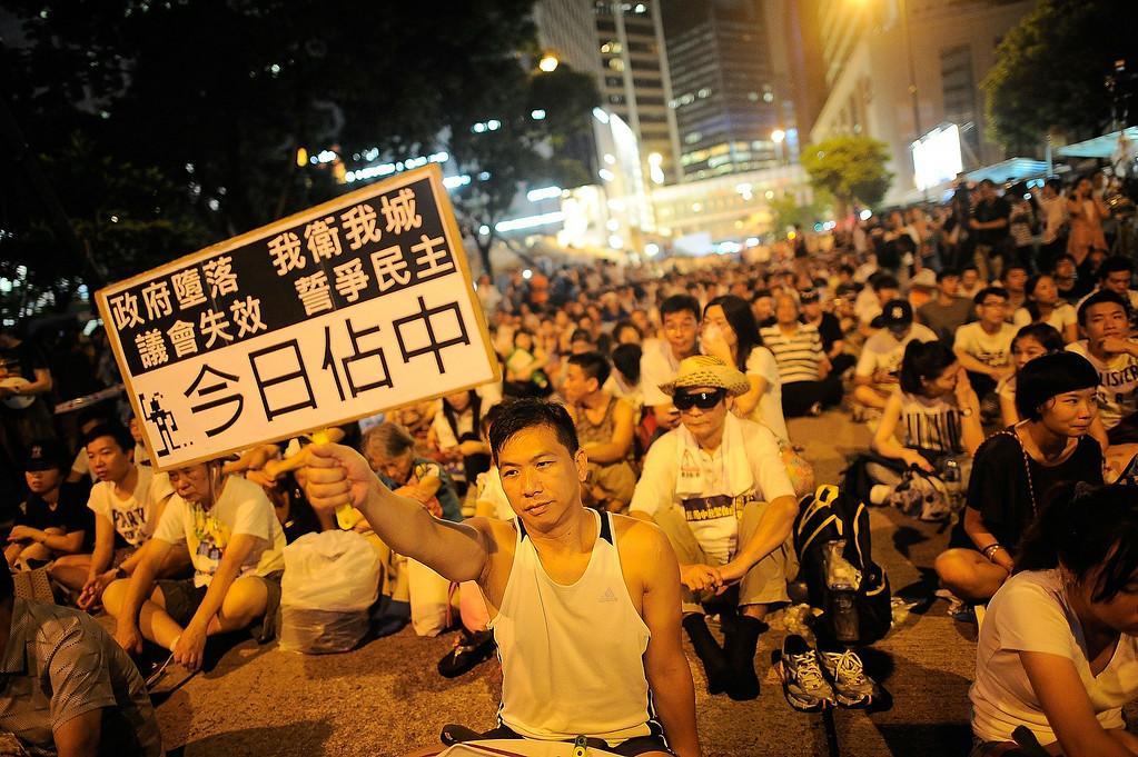 . A protester holds a placard during the annual pro-democracy protest on July 1, 2014 in Hong Kong. Seventeenth anniversary of Hong Kong\'s return to China rule is marked in July 1, and tens of thousands of Hong Kong residents marched on the street to demand for universal suffrage for city\'s next leader.  (Photo by Anthony Kwan/Getty Images)