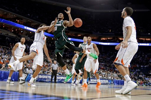 . Michigan State\'s Marvin Clark Jr. (0) is fouled by Virginia\'s Anthony Gill (13) during the first half of an NCAA tournament college basketball game in the Round of 32 in Charlotte, N.C., Sunday, March 22, 2015. (AP Photo/Gerald Herbert)