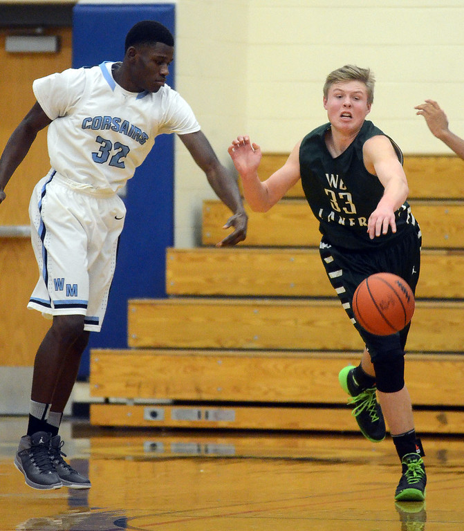 . West Bloomfield\'s #33 Zach Allread steals a pass in front of Waterford Mott\'s #32 Dmonta Harris during their game at Waterford Mott High School, Thursday December 12, 2013. West Bloomfield went on to win the game 55-52. (Vaughn Gurganian-The Oakland Press)
