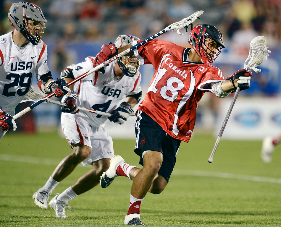 . American players Lee Zink (29) and Daniel Burns (4) shadowed Canada midfielder Cam Zink (18) during his run in the second half. The United States defeated Canada 10-7 in the opening game of the FIL World Lacrosse Championships Thursday night, July 10, 2014.   Photo by Karl Gehring/The Denver Post